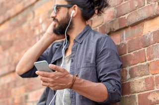 people and technology concept - close up of man with earphones and smartphone listening to music at brick wall on street