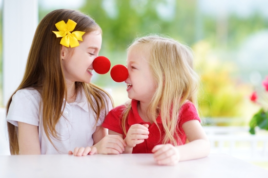 Happy Little Sisters Wearing Red Clown Noses Having Fun Together
