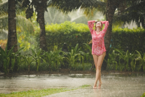 Beautiful woman under the tropical rain