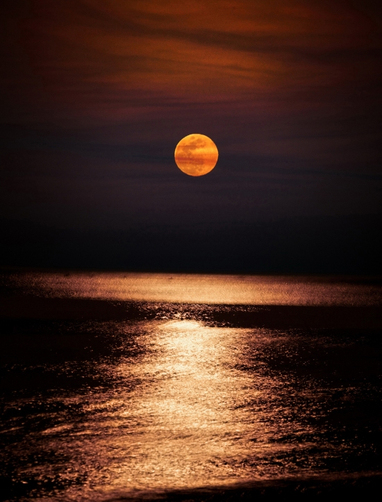 Big full moon over the ocean surface