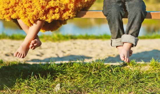 Girl And Boy With Bare Feet Sit On A Bench Near The Spring Sprin