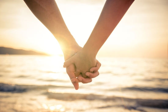 Couple Holding Hands At Sunset