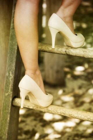 close up of woman in high heels climbing up a ladder in nature